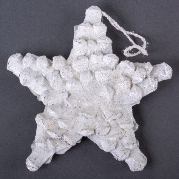 This is an image of a star shaped decoration, made from pine cone petals. It has been painted white and dusted with glitter.