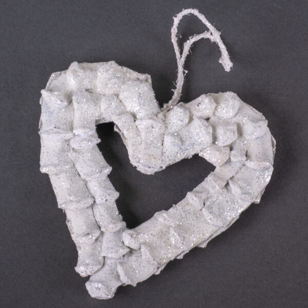 This is an image of a heart shaped decoration, made from pine cone petals. It has been painted white and dusted with glitter.