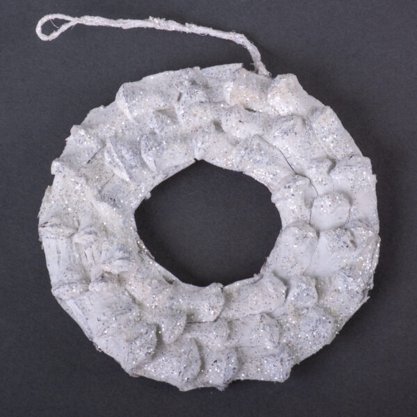 This is an image of a wreath shaped decoration, made from pine cone petals. It has been painted white and dusted with glitter.