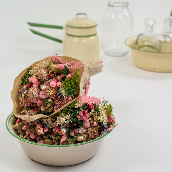 This image shows a styled image of a bunch of Sorriso mix, pink, nestled in an old fashioned enamelled bowl, with some more retro pots and glass in the background