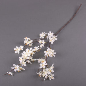 This image shows a faux apple blossom stem laid on a grey background.