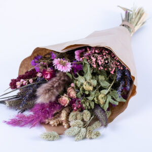 This image shows a pre-made wildflower bouquet, contain a mix of flowers with pink hues.