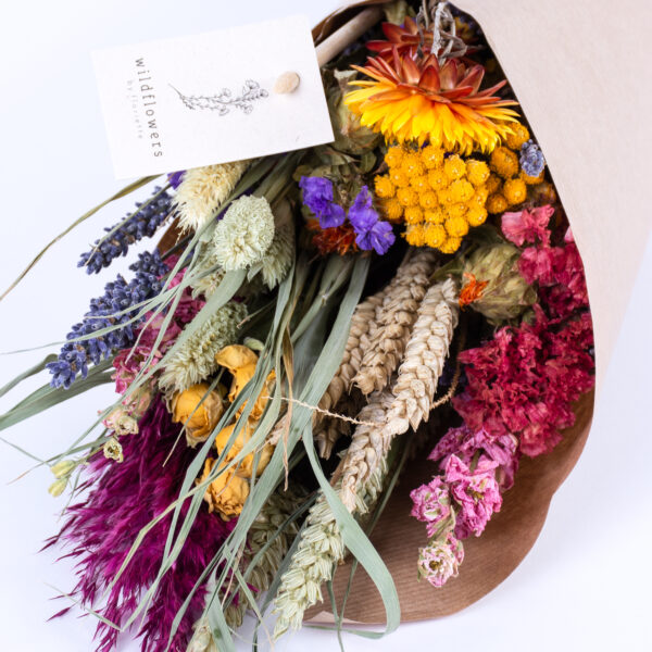 This image shows a pre-made wildflower bouquet, contain a mix of flowers with a variety of colourful blooms.