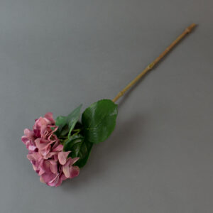 This image shows a faux, burgundy hydrangea stem on a grey background