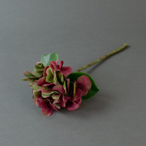 This image shows a faux, pink and green hydrangea stem on a grey background