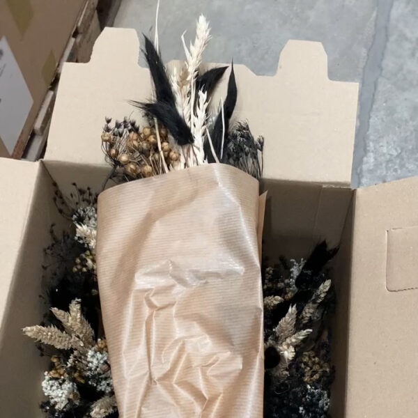 This image shows a single bouquet from a bucket of mixed wildflowers. The bouquet lays across the top of the box of the remaining bouquets within the pack.