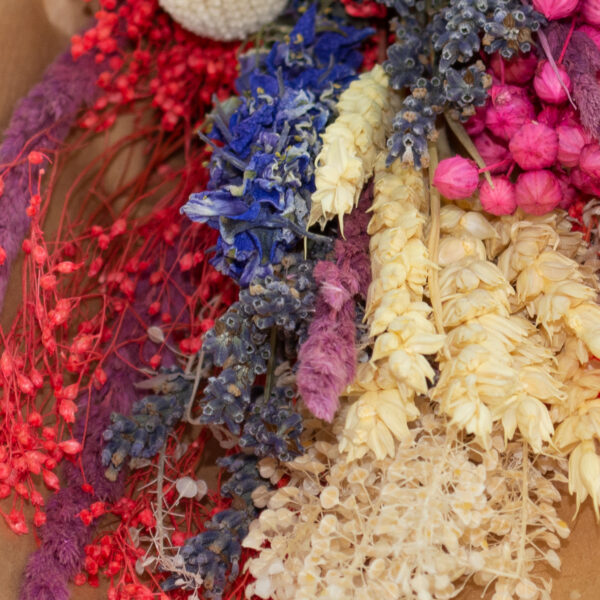 This is a close up image of a mixed dried flower summer bouquet wrapped in kraft paper.