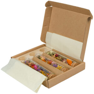 This image shows a small box, containing three glass vials full of wild, dried flowers, and a corresponding wooden block with three recesses, designed for the vials to be displayed.