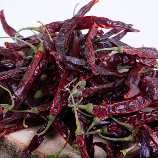 This image shows dried, whole, red chillies scattered on some wood slices, against a white background